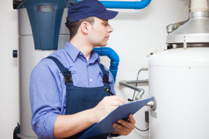 Technician looking at conventional water heater