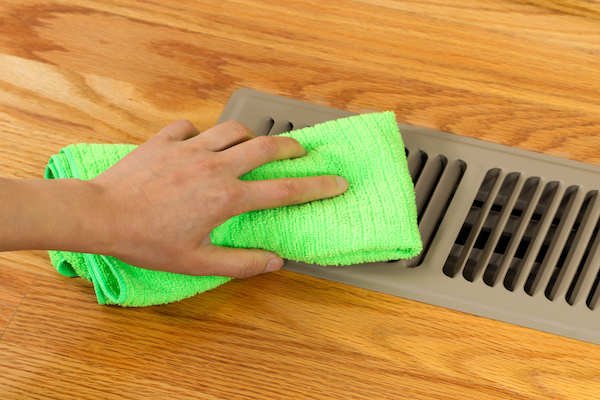gloved hand cleaning air vent