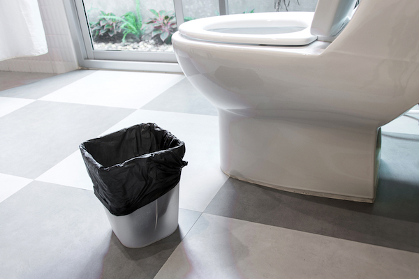 Small plastic garbage can with black garbage bag liner in bathroom next to toilet