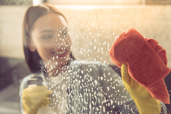 woman smiling as she cleans shower wall