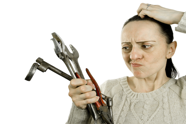 Woman looking at handful of tools with confused expression and scratching her head