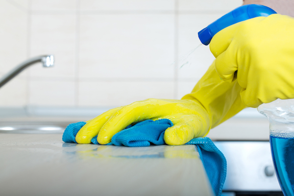 Gloved hand wiping counter with washcloth