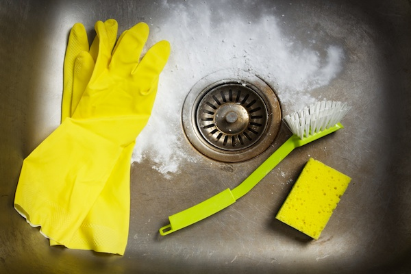 White cleaner in sink with yellow gloves, sponge, and brush