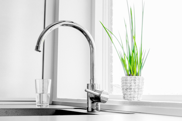 Long stainless steel faucet next to green grass in a white basket.