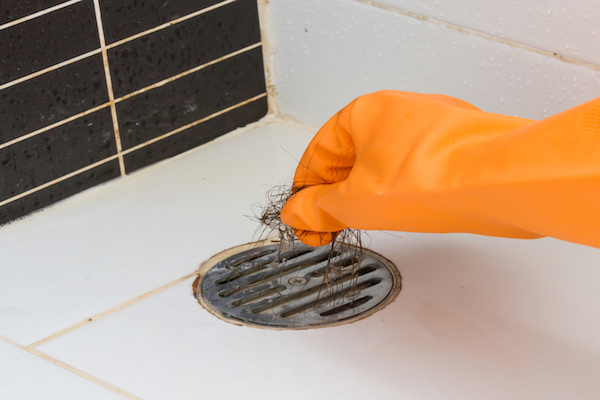 Gloved hand pulling hair out of shower drain