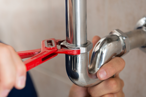 Person using drain wrench pliers to remove slip nut from top of overflow pipe on p-trap