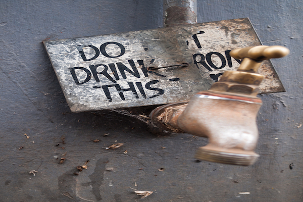 "rusty old faucet with wooden sign balanced on it. Sign reads ""DO NOT DRINK FROM THIS"""