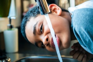 A young person drinks water from a kitchen faucet.