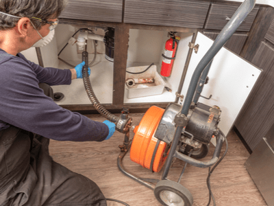 A plumber uses an auger to unclog a kitchen sink.
