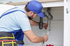 Man in a light blue shirt with dark blue suspenders and a blue hat fixing the pipes under a sink drain