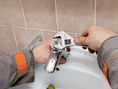 A homeowner removes a faucet cartridge to fix a leak.