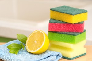 A lemon and stack of multi colored sponges