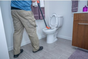A person uses a toilet auger on their overflowing toilet.