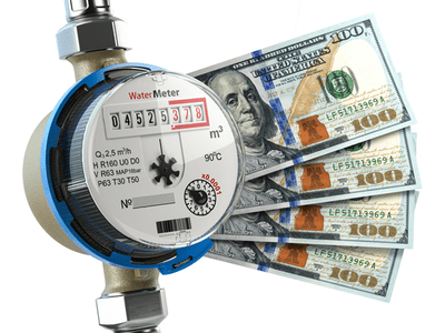A water meter with money fanned out from the side.