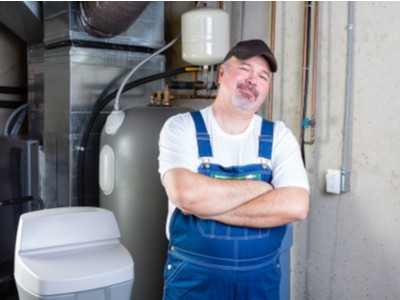 A plumbing technician stands next to a home water softener.