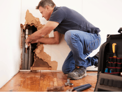 A plumber fixes pipes behind a water damaged wall.