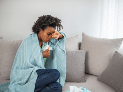 A woman with mold-related illness rests on her couch.