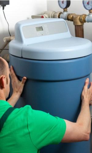 A plumbing technician installing a new water softener.