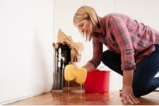 Women in plaid shirt on the floor wiping up water with a yellow sponge due to exposed leaking pipes in her wall