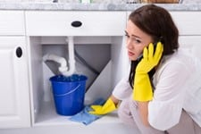 Women on cell phone on the floor under the sink with a blue bucket placed under leaking pipes