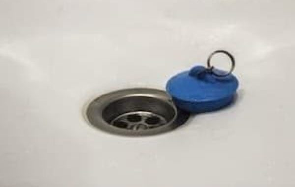 Bathtub drain with a rubber stopper next to it