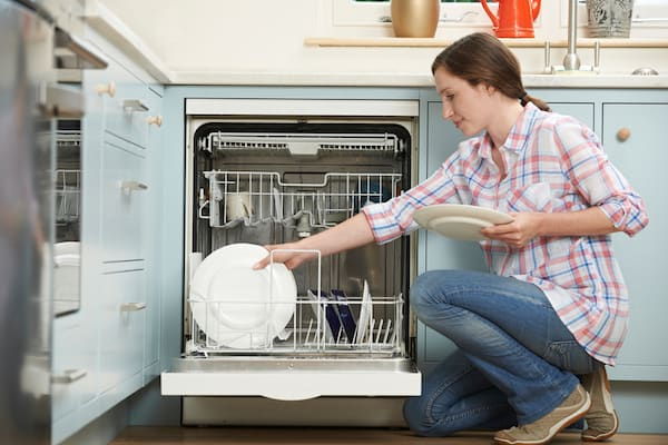 Woman putting dishes into her dishwasher