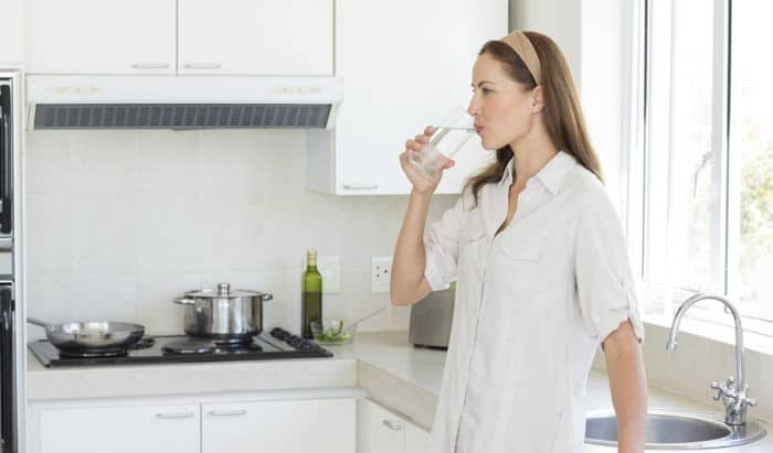 A woman takes a drink of water.