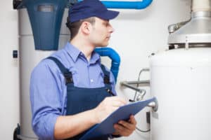 Plumbing professional conducting routine inspection of home's water heater.