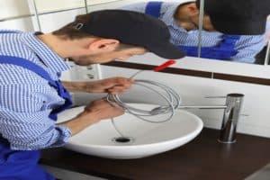 plumber using plumber's snake