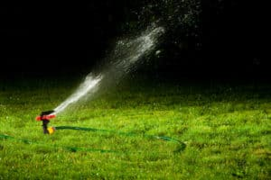 Sprinkler watering a lawn at night