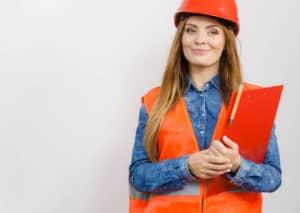Female construction foreman in orange hardhat and vest with clipboard