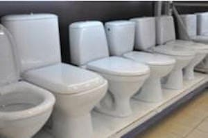 Several different types of possible replacement toilets lined up at a store