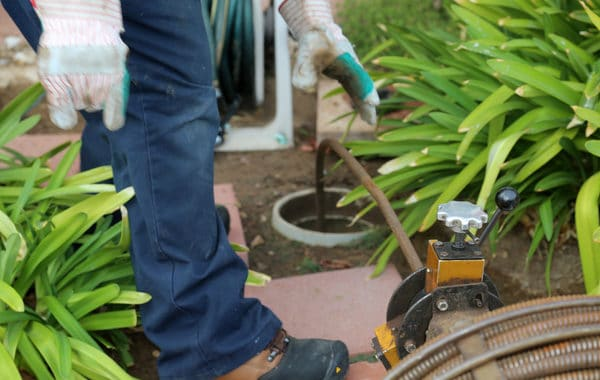 plumbing using an auger to clean out a home sewer