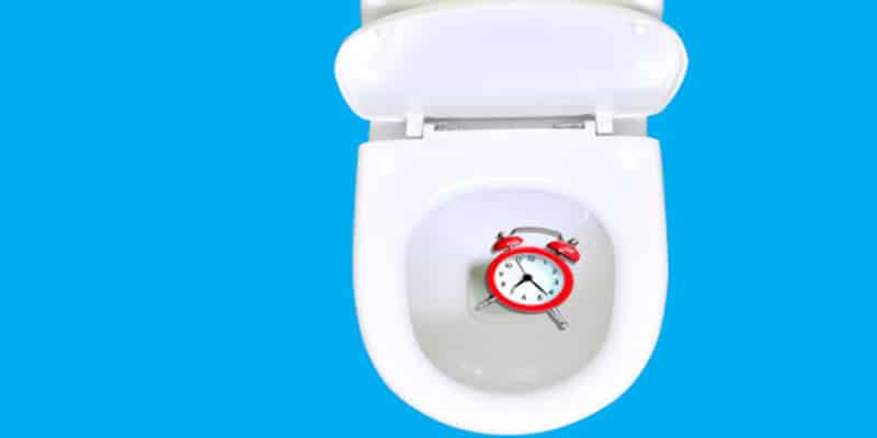 Clock in toilet against blue background