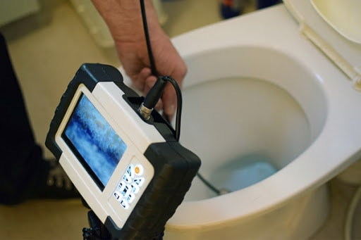 A video monitor records a plumbing inspection camera.