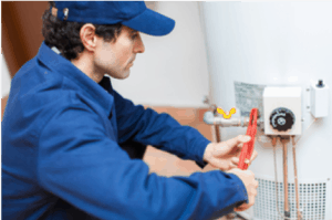 plumber in blue fixing a water heater
